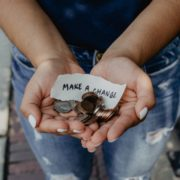 "A picture of a woman holding up spare change in the palms of her hands, with a sign that says ""Make A Change."""